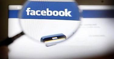 A Facebook logo on a computer screen is seen through a magnifying glass in Bern