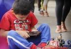 CIUDAD DE MÉXICO, 22MAYO2016.- Un niño deja de lado sus juguetes para entretnerse con el celular de su madre, durante la clase de yoga en el Ángel de la Independencia.  FOTO: PAULINA NEGRETE /CUARTOSCURO.COM
